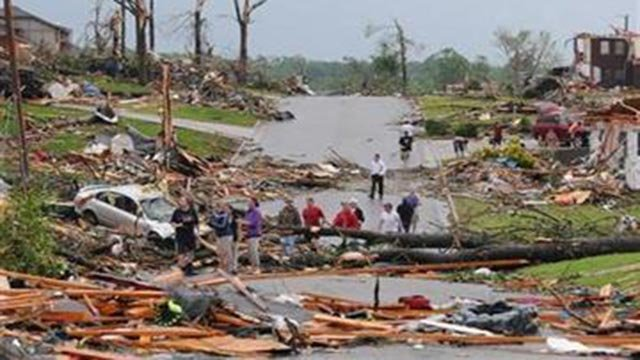 Residents of Joplin, Mo, survey the damage after a tornado hit the city on Sunday, May 22, 2011. The tornado tore a path a mile wide and four miles long destroying homes and businesses. (AP Photo/Mike Gullett)