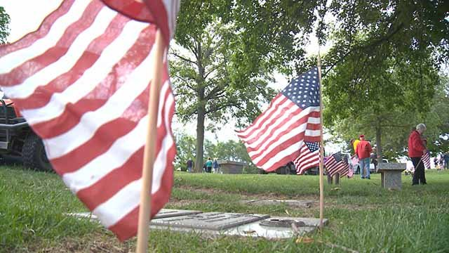 Volunteers placed American flags on graves at St. Charles Memorial Gardens Wednesday. Credit: KMOV