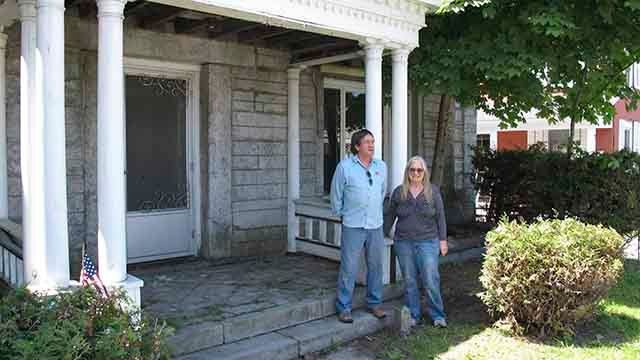 In this photo taken on June 8, 2017 in Derby, Vt., Brian and Joan Dumoulin pose on both sides of a marker showing the U.S.-Canadian border in the front yard of their home. She is in Canada, while he is in the United States. Straddling the border between t