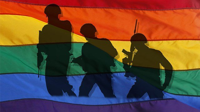 Silhouette of soldiers on patrol over rainbow flag. (AP Images)