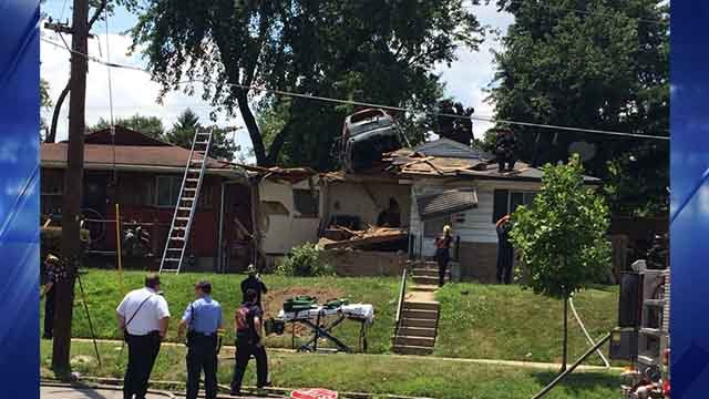 Authorities were called to the 5900 block of Lillian, where a car was lodged into the roof of a house (Credit: KMOV)