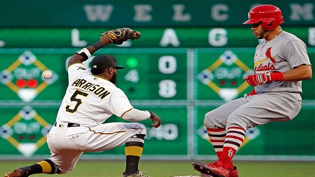 The relay throw gets away from Pittsburgh Pirates second baseman Josh Harrison (5) as St. Louis Cardinals' Tommy Pham pulls safely into second with a double and a run-batted-in in the fifth inning. (APImages)