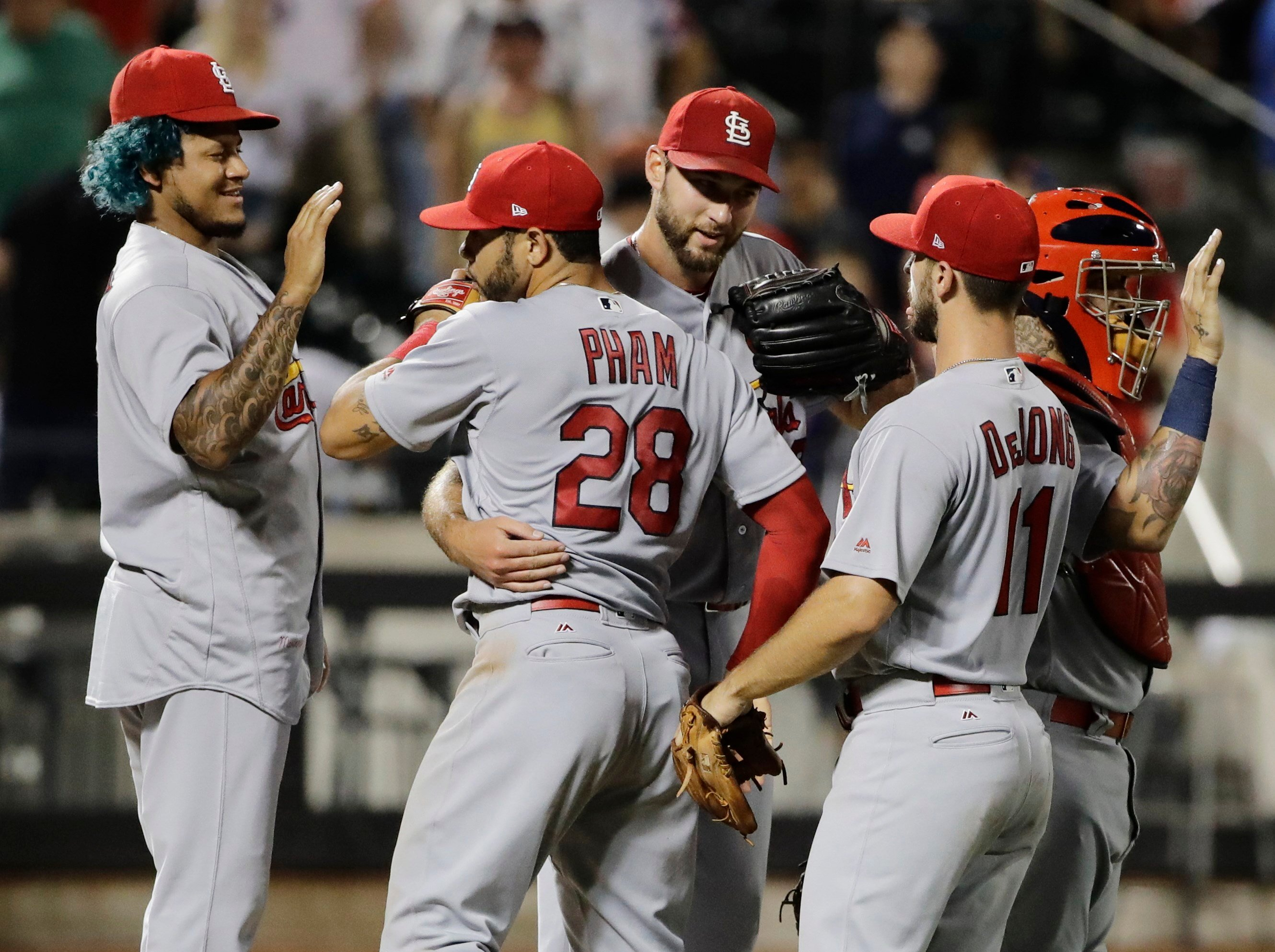 St. Louis Cardinals' Carlos Martinez, left, and Paul DeJong, right watch as Tommy Pham (28) hugs pitcher Michael Wacha after the Cardinals defeated the New York Mets 5-0 in a baseball game Tuesday, July 18, 2017, in New York. (AP Photo/Frank Franklin II)