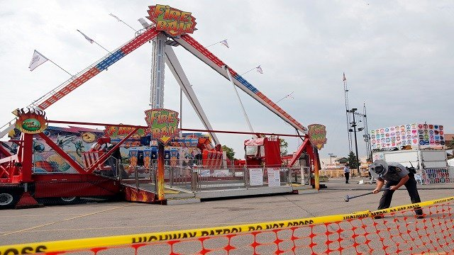 An Ohio State Highway Patrol trooper removes a ground spike from in front of the fire ball ride at the Ohio State Fair Thursday. (Credit: Associated Press)