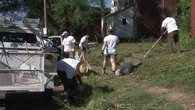 Volunteers with Better Family Life work to clean up neighborhoods in North St. Louis on Saturday, July 29, 2017 (Credit: KMOV)