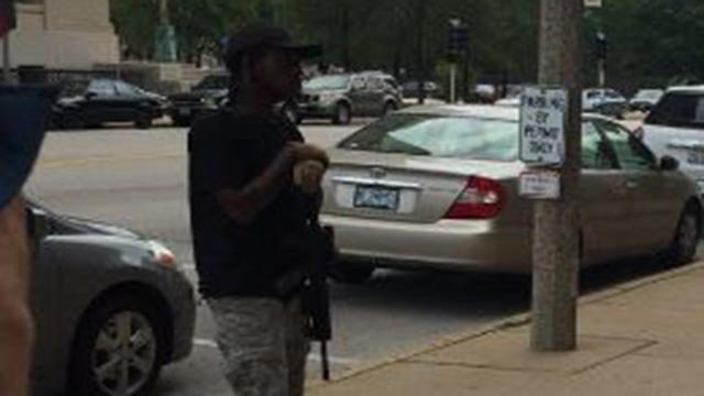 A man carrying a rifle was outside the courthouse Tuesday (Credit: Lauren Trager / News 4)