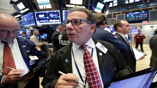 Trader Sal Suarino, center, works on the floor of the New York Stock Exchange, Tuesday, Aug. 1, 2017. More solid earnings reports from U.S. companies are sending stocks higher in early trading on Wall Street. (AP Photo/Richard Drew)