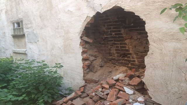 Bricks are spilling over into the neighbor's yard from this abandoned home. (Credit: KMOV)