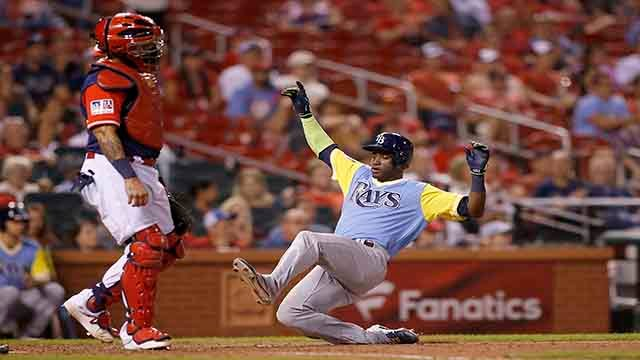 St. Louis Cardinals catcher Yadier Molina stands near the plate as Tampa Bay Rays' Adeiny Hechavarria scores during the ninth inning of a baseball game Friday, Aug. 25, 2017, in St. Louis. The Rays won 7-3. (AP Photo/Scott Kane)
