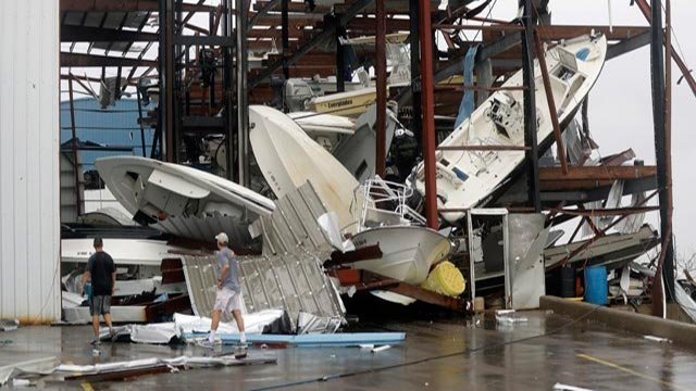 Men checks on a boat storage facility that was damaged by Hurricane Harvey, Saturday, Aug. 26, 2017, in Rockport, Texas.  (AP Photo/Eric Gay)