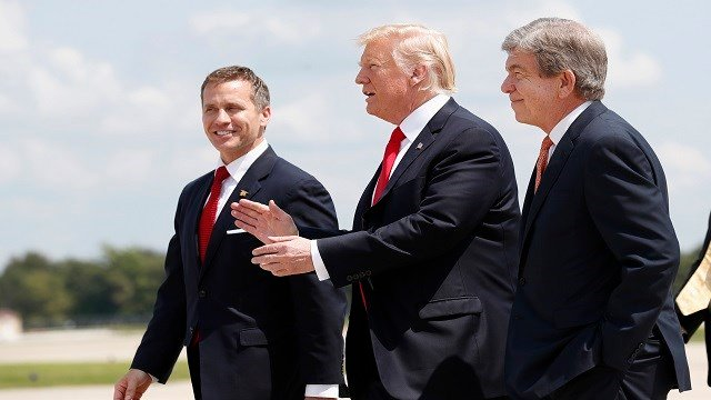 President Donald Trump, flanked by Missouri Gov. Eric Greitens, left, and Sen. Roy Blunt, R-Mo., talk as they arrive in Springfield, Mo., Wednesday, Aug. 30, 2017. (AP Photo/Alex Brandon)