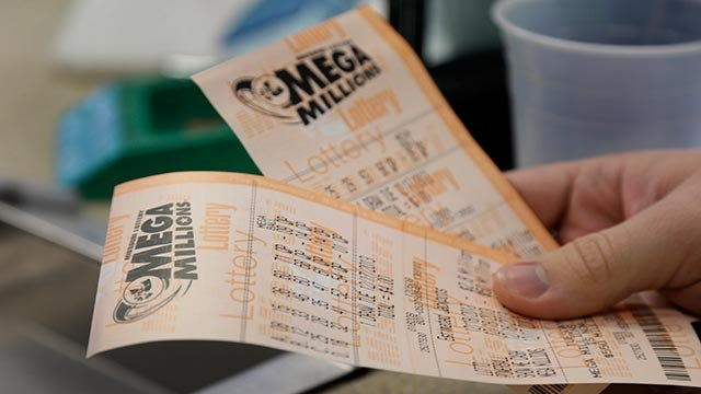 Scott Hoormann holds two Mega Millions lottery tickets he purchased in St. Louis (Credit: AP Photo / Jeff Roberson)