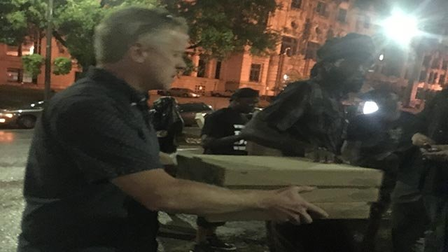 Chris Sommers, the co-founder of Pi Pizza, handing out pizza during protests in the Central West End Friday night. (Credit: Alexis Zotos)