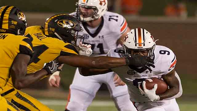 Auburn running back Kam Martin, right, has his face mask grabbed by Missouri's Terez Hall, left, as he runs the ball during the third quarter of an NCAA college football game Saturday, Sept. 23, 2017, in Columbia, Mo. Auburn won the game 51-14. (AP Photo/