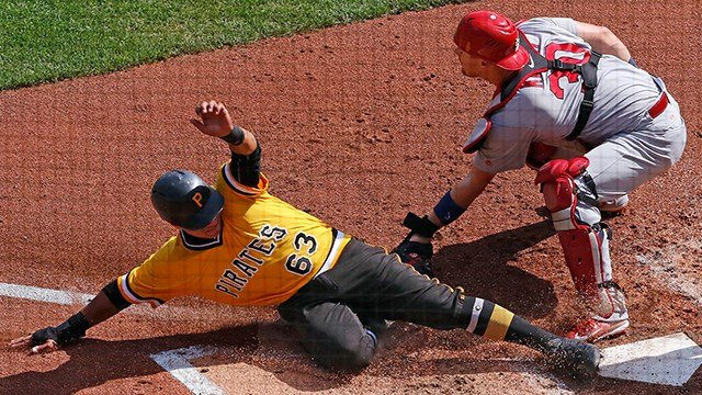 Pittsburgh Pirates' Chris Bostick (63) scores on a sacrifice fly to right field by Pirates' Elias Diaz ahead of the tag by St. Louis Cardinals catcher Carson Kelly in the third inning of a baseball game, Sunday, Sept. 24, 2017 in Pittsburgh. (AP Photo)