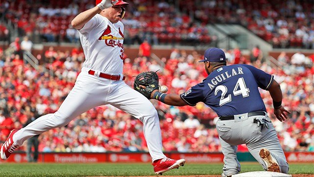 St. Louis Cardinals' Aledmys Diaz, left, is out at first as Milwaukee Brewers first baseman Jesus Aguilar handles the throw during the second inning. (AP Photo)