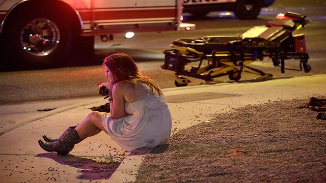 A woman sits on a curb at the scene of a shooting outside of a music festival along the Las Vegas Strip, Monday, Oct. 2, 2017, in Las Vegas. Multiple victims were being transported to hospitals after a shooting late Sunday (AP Photo/John Locher)