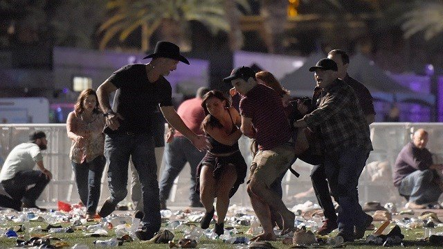 People carry a person at the Route 91 Harvest country music festival after apparent gun fire was heard on October 1, 2017 in Las Vegas, Nevada. There are reports of an active shooter around the Mandalay Bay Resort and Casino. (David Becker / Getty)
