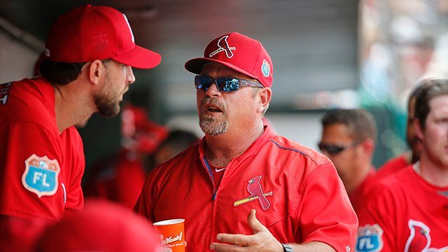 St. Louis Cardinals', left, Adam Wainwright, talks with the pitching coach Derek Lilliquist in the dugout, during the fifth inning of an exhibition spring training baseball game against the Detroit Tigers in Jupiter, Fla. (AP Photo/Brynn Anderson)