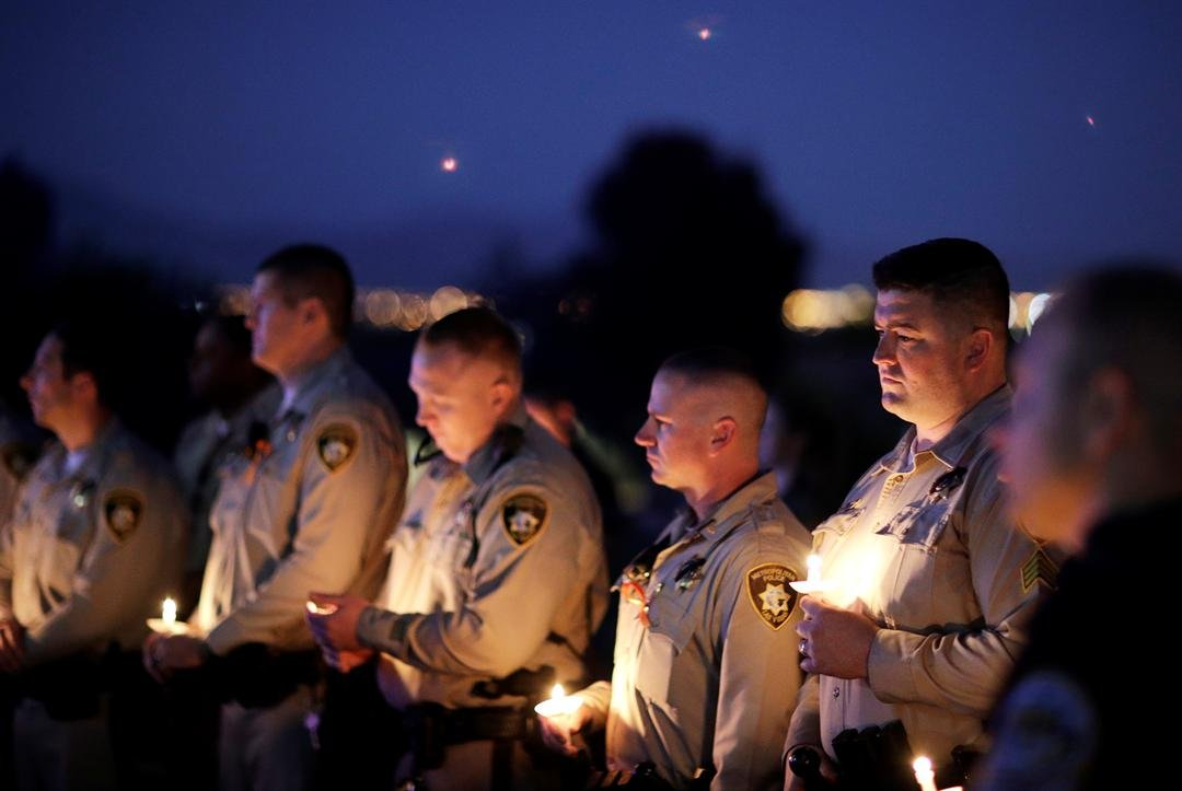 Las Vegas police Sgt. Ryan Fryman, right, and other officers attend a candlelight memorial for Las Vegas police officer Charleston Hartfield, Thursday, Oct. 5, 2017, in Las Vegas. (AP Photo)