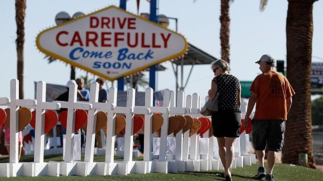 People walk by crosses placed near Las Vegas' famous sign Thursday, Oct. 5, 2017, in Las Vegas. (AP Images)