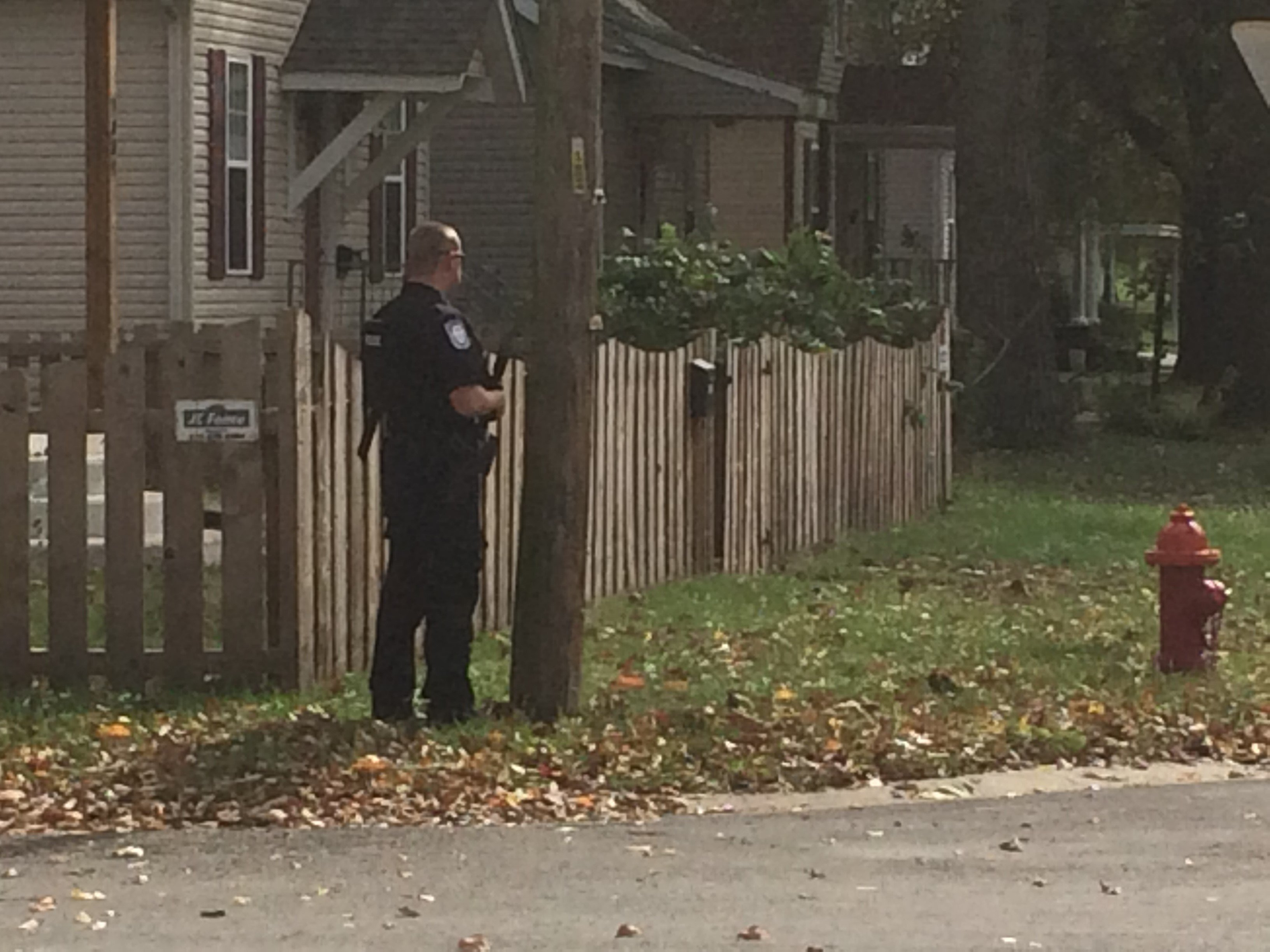 An officer outside a home in Highland Tuesday (Credit: Bryce Moore)