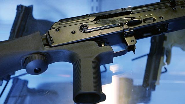 "A device called a ""bump stock"" is attached to a semi-automatic rifle at the Gun Vault store and shooting range in South Jordan, Utah. (Credit: AP Photo / Rick Bowmer)"