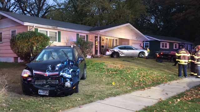 A witness said the driver of a black SUV lost control before the SUV struck a silver car in the home's driveway, pushing the silver car into the house. Credit: KMOV