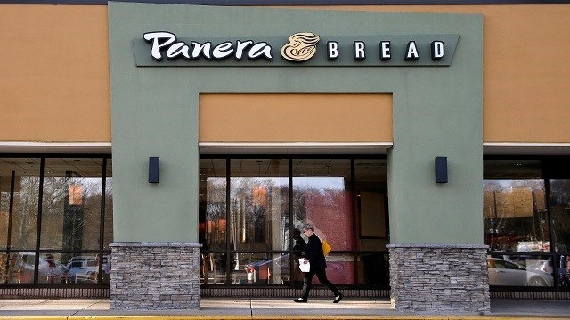 FILE - In this Wednesday, April 12, 2017, file photo, a passer-by walks near an entrance to a Panera Bread restaurant in Natick, Mass. In a deal announced Wednesday, Nov. 8, 2017, Panera Bread says it is buying bakery chain Au Bon Pain to boost its presen