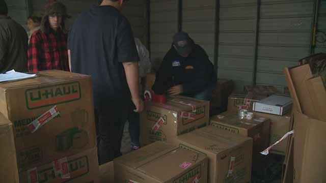 Volunteers pack up packages for soldiers overseas. Credit: KMOV