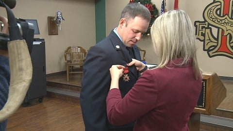 Johnathan Vallero's wife pins the Medal of Valor on the firefighter. (Credit: KMOV)