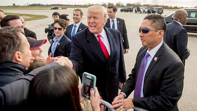 President Donald Trump greets visitors on the tarmac as he arrives at St. Louis Lambert International Airport, Wednesday, Nov. 29, 2017, in St. Louis, where he will speak about tax reform. (AP Photo/Andrew Harnik)