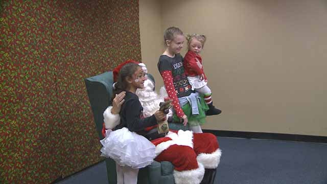 Several kids pose for pictures with Santa at the Motion for Kids Holiday Party. Credit: KMOV