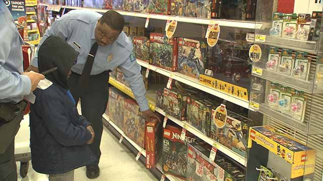 An officer helps a child pick out a present during the 9th annual Patrolling for Presents event at Target in South City. Credit: KMOV