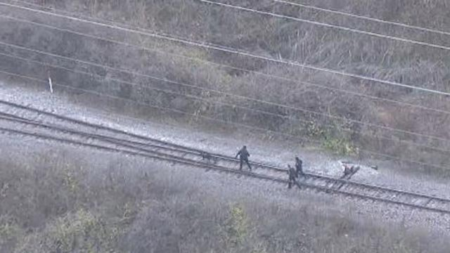Officers walking railroad tracks with a K-9 Tuesday (Credit: KMOV)