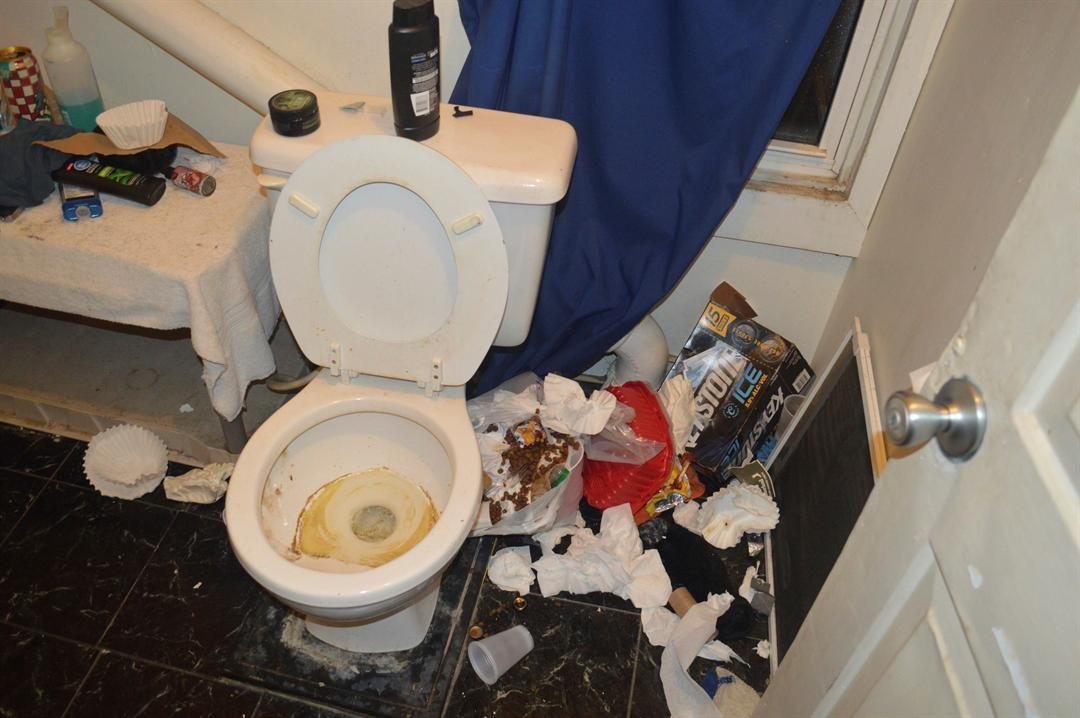 Filthy conditions inside a bathroom at a house belonging to an unsanctioned fraternity near Brockport College are shown.  (Brockport Police Department via AP)