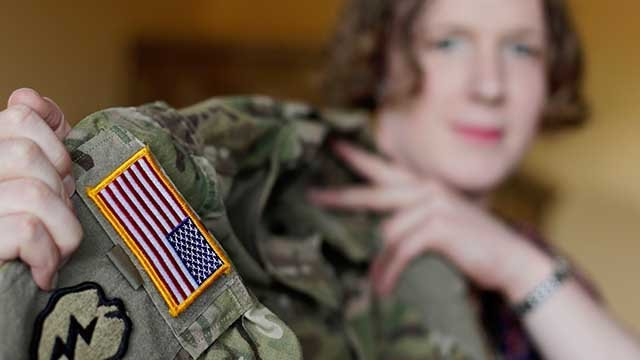 In this July 29, 2017 photo transgender U.S. army captain Jennifer Sims lifts her uniform during an interview with The Associated Press in Beratzhausen near Regensburg, Germany. (AP Photo/Matthias Schrader)