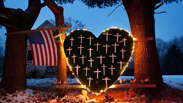 In this Dec. 14, 2013 file photo, a makeshift memorial with crosses for the victims of the Sandy Hook Elementary School shooting massacre stands outside a home in Newtown, Conn., on the one-year anniversary of the shootings. (Credit: AP Photo)