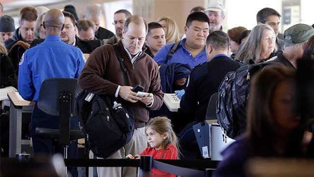 Travelers wait in line to check in at a security checkpoint area at Midway International Airport, Friday, Nov. 21, 2014, in Chicago.  (AP Photo/Nam Y. Huh)