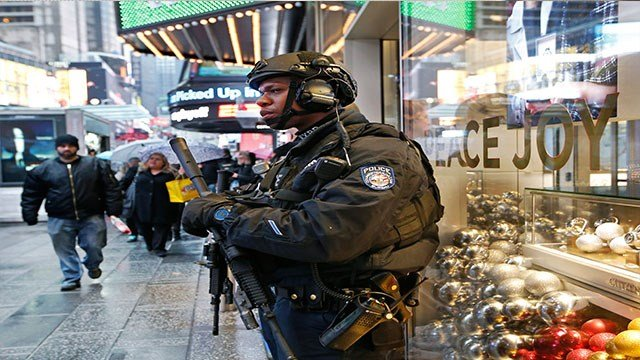 A heavily armed counterterrorism officer takes shelter beneath an overhang above a store in Times Square in New York.  (AP Photo/Kathy Willens, File)