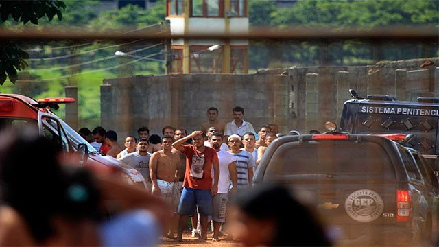 Prisoners, back, try to contact relatives after a rebellion at the Colonia Agroindustrial prison in the Aparecida de Goiania Complex, in the state of Goias, Brazil, Monday, Jan. 1, 2018. (Claudio Reis/O Popular via AP)