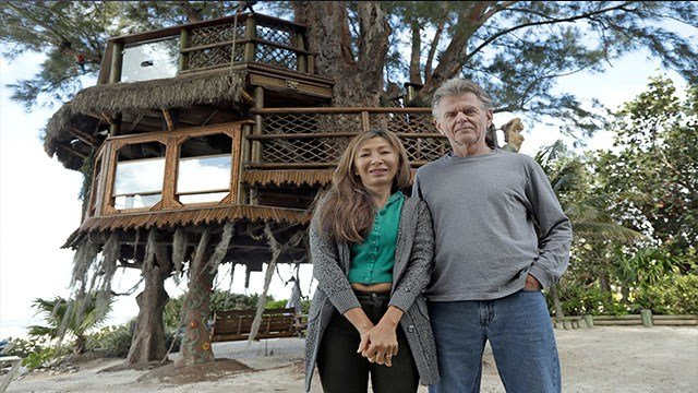 Lynn Tran and her husband Richard Hazen pose  near their Australian pine treehouse Thursday, Jan. 4, 2018, in Holmes Beach, Fla. (AP Photo/Chris O'Meara)