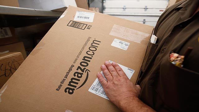 In this Oct. 18, 2010 file photo, United Parcel Service (UPS) driver Paul Musial lifts an Amazon.com box in Palo Alto, Calif. (Credit: AP Photo / Paul Sakuma, File)
