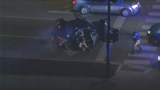 Suspects flee from a stolen Porsche in downtown Chicago following a police chase. (Credit: CNN)
