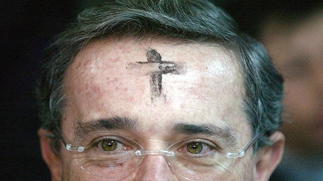 Colombian President Alvaro Uribe is seen with an ash cross on his forehead on Ash Wednesday (Credit: AP Photo / William Fernando Martinez)