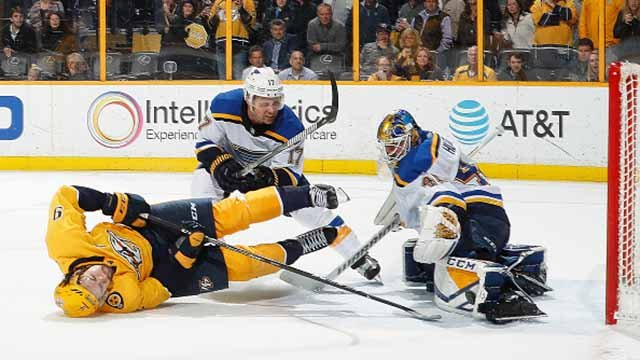 Jaden Schwartz #17 of the St. Louis Blues takes Filip Forsberg #9 of the Nashville Predators to the ice as he shoot the puck against goalie Carter Hutton #40 in overtime during an NHL game at Bridgestone Arena on February 13, 2018. Credit: Getty Images
