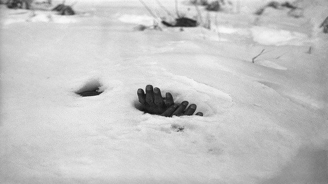 A pair of bound hands and a breathing hole in the snow at Yangji, Korea, Jan. 27, 1951 reveal the presence of the body of a Korean civilian shot and left to die by retreating Communists during the Korean War. (AP Photo/Max Desfor)