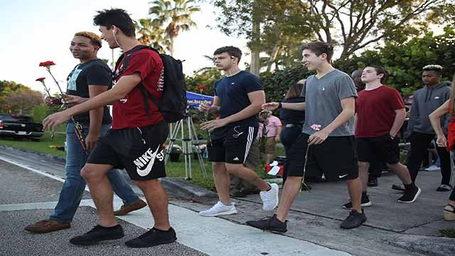 Students walk to Marjory Stoneman Douglas High School as they attend classes for the first time since the shooting that killed 17 people on February 14 at the school on February 28, 2018 in Parkland, Florida. (Getty Image)
