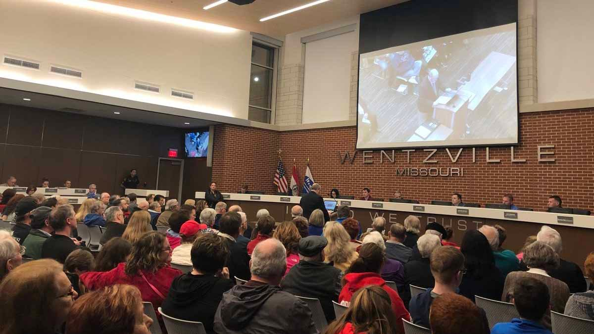 "Hundreds filled Wentzville's city council chambers to voice their opinions on a sign that reads ""In God We Trust"" that is inside the council chambers. Credit: KMOV"