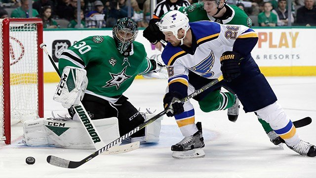 Dallas Stars goalie Ben Bishop (30) gets help from defenseman Esa Lindell (23) of Finland against pressure at the net by St. Louis Blues center Kyle Brodziak (28) in the second period of an NHL hockey game Saturday, March 3, 2018, in Dallas. (AP Photo/Ton